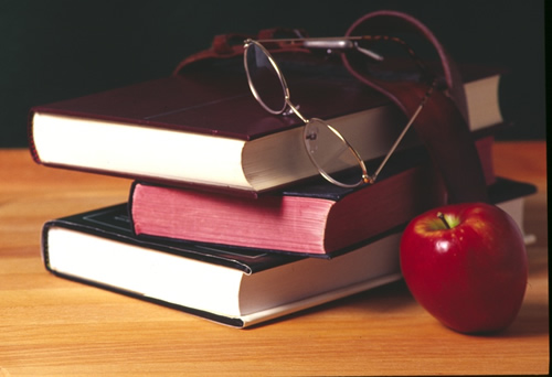 Stacked books on a desk with glasses and an apple.