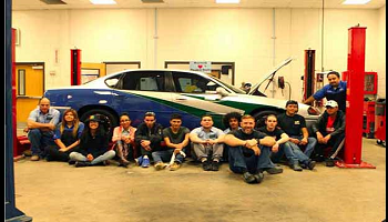 Maxwell students sitting in front award winning vehicle