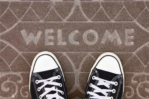 """Welcome"" sign on a doormat"