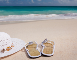 white hat with sandals on sand with ocean in background