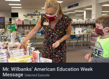 Mrs. Reynolds and Brookwood Elementary  student select books in a still from Mr. Wilbanks' message