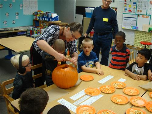 Mrs. Durbin carves a pumpkin with students.