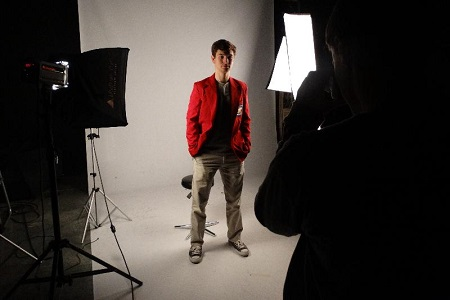Male student posing for a picture in the professional photography studio