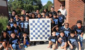 Chess Club students and teacher volunteers are smiling at the camera holding a chess board.